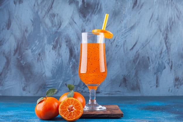 Um copo de suco com canudo e tangerinas inteiras e fatiadas.