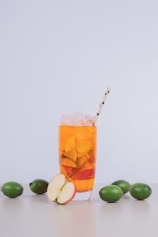 Um copo de suco com fatias de frutas e frutas frescas.