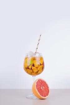 Um copo de suco com fatias de frutas e toranja na parede branca.
