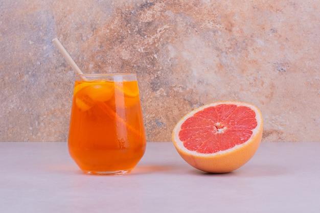 Um copo de suco com frutas cítricas dentro