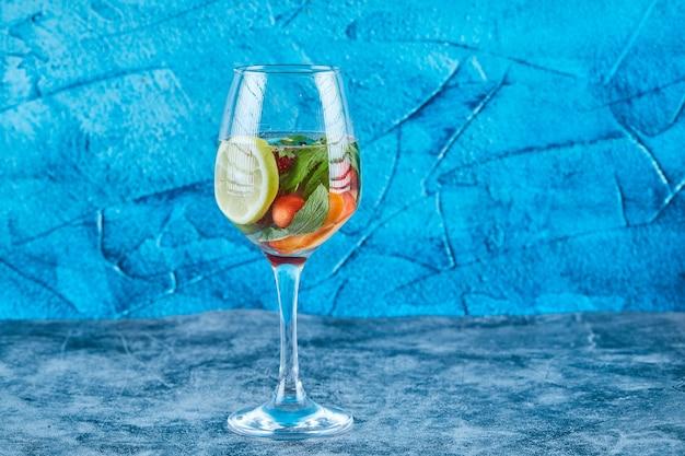 Um copo de suco com frutas inteiras dentro sobre uma superfície azul