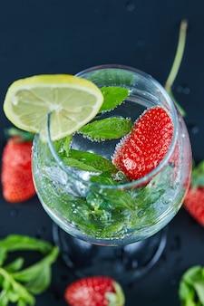 Um copo de suco com frutas inteiras e uma fatia de limão dentro em uma superfície escura