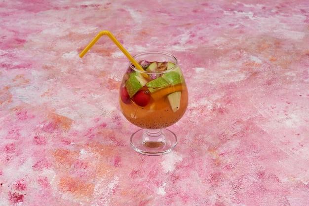 Um copo de suco com frutas mistas.