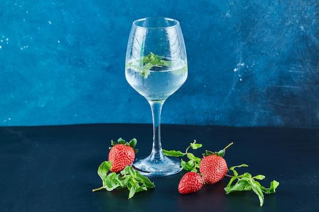 Um copo de suco com hortelã e morangos frescos e hortelã na superfície azul
