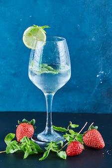 Um copo de suco com hortelã e uma fatia de limão na superfície azul com morangos frescos e hortelã