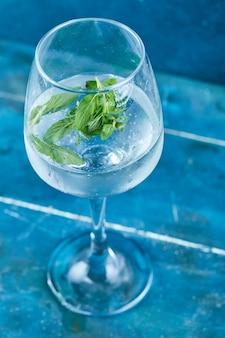 Um copo de suco com hortelã na superfície azul