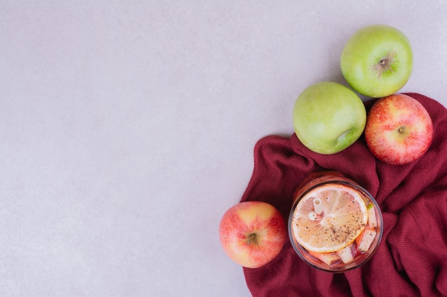 Um copo de suco com maçãs na toalha vermelha
