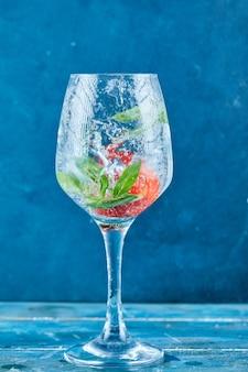 Um copo de suco com morangos e hortelã dentro na superfície azul
