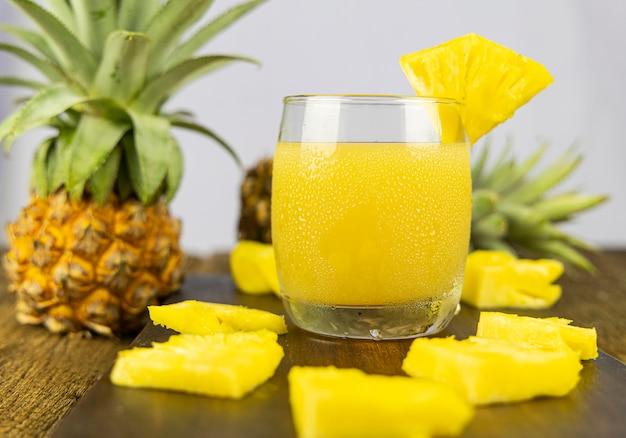 Um copo de suco de abacaxi com uma fatia de abacaxi no fundo da mesa de madeira.