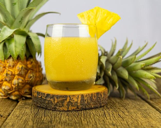 Um copo de suco de abacaxi no fundo da mesa de madeira.
