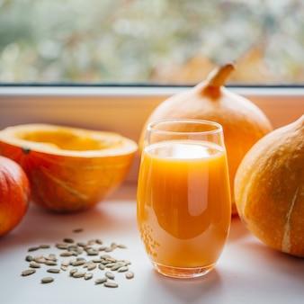 Um copo de suco de abóbora com sementes de abóbora em uma janela