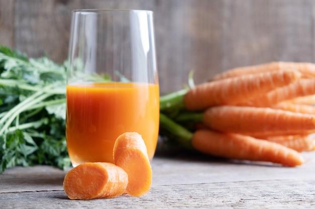 Um copo de suco de cenoura e um monte de cenouras frescas ao lado na madeira
