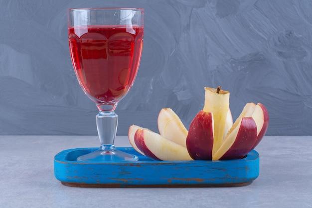 Um copo de suco de cereja e fatias de maçã em uma placa de madeira na mesa de mármore.
