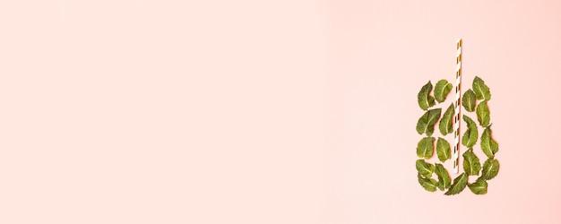 Um copo de suco de folhas de hortelã e palha em um rosa claro