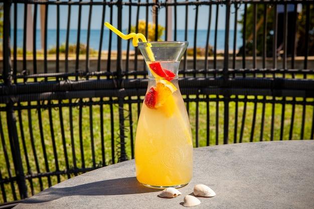 Um copo de suco de frutas com o mar. vista lateral.