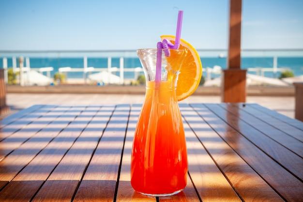 Um copo de suco de frutas no chão com praia, vista lateral.