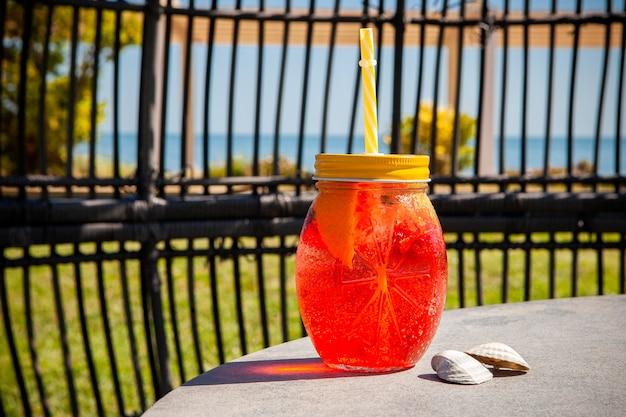 Um copo de suco de frutas vista lateral com o mar