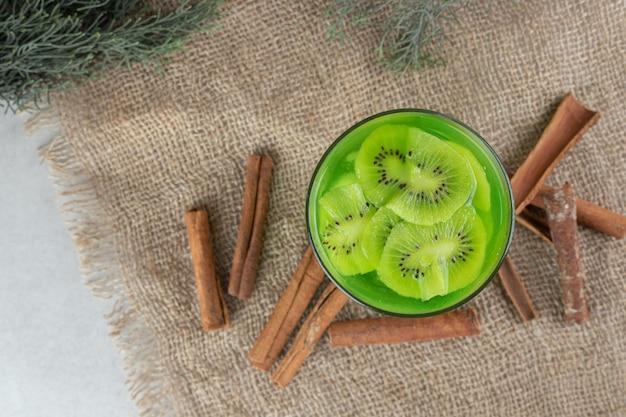 Um copo de suco de kiwi e paus de canela na serapilheira.