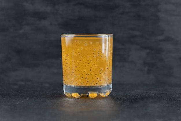 Um copo de suco de laranja amarelo no preto