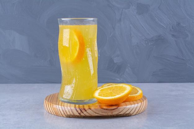 Um copo de suco de laranja ao lado de uma fatia de laranja em uma placa de madeira na mesa de mármore.