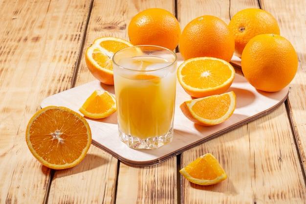Um copo de suco de laranja com cubos de gelo e uma placa de madeira com laranjas em uma mesa de madeira. suco de laranja espremido na hora.