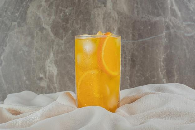 Um copo de suco de laranja com cubos de gelo em tecido de cetim