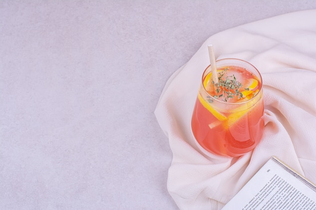 Um copo de suco de laranja com ervas e especiarias