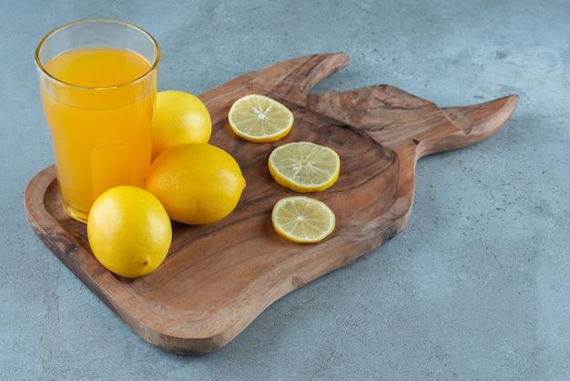 Um copo de suco de laranja com limões frescos.