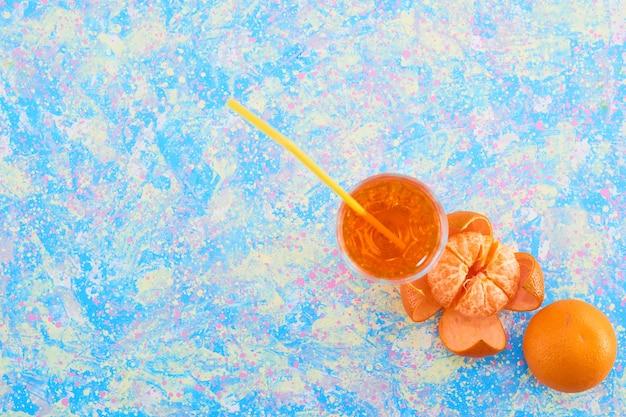 Um copo de suco de laranja com tangerinas ao redor, vista de cima