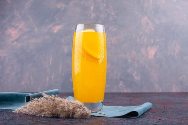 Um copo de suco de laranja com uma fatia de fruta colocado em um colorido.