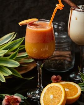 Um copo de suco de laranja decorado com casca de laranja