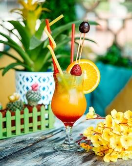 Um copo de suco de laranja decorado com morango, fatia de laranja e cereja