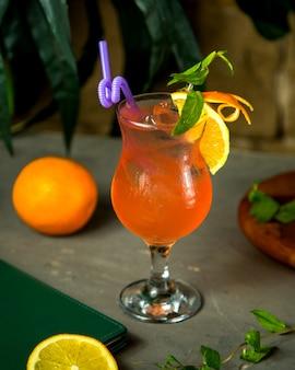 Um copo de suco de laranja decorado com raspas de laranja e hortelã