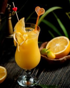 Um copo de suco de laranja decorado com raspas de laranja
