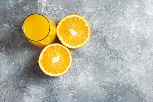 Um copo de suco de laranja e fatias de laranja.