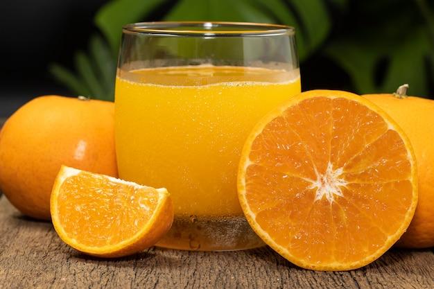 Um copo de suco de laranja e frutas de laranja cortadas ao meio na mesa de madeira.