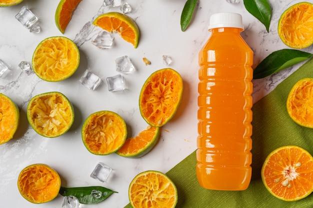 Um copo de suco de laranja e frutas frescas no chão com cubos de gelo.