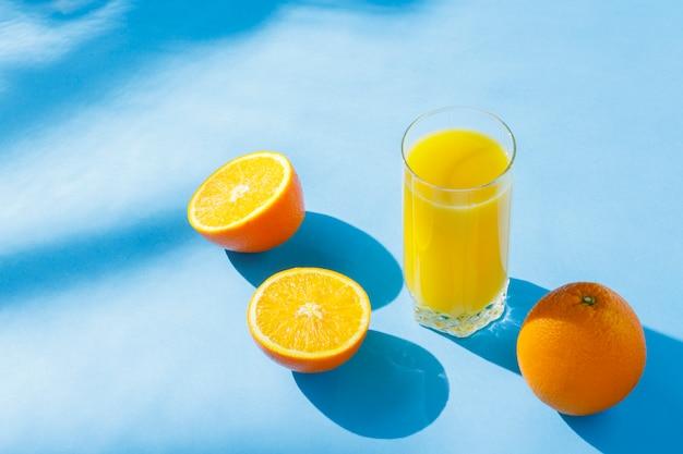 Um copo de suco de laranja e laranjas em um fundo azul. conceito de vitaminas, tropical, verão. luz natural. vista plana leiga, superior.