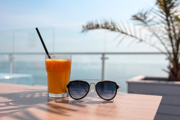 Um copo de suco de laranja e óculos de sol no fundo do mar.