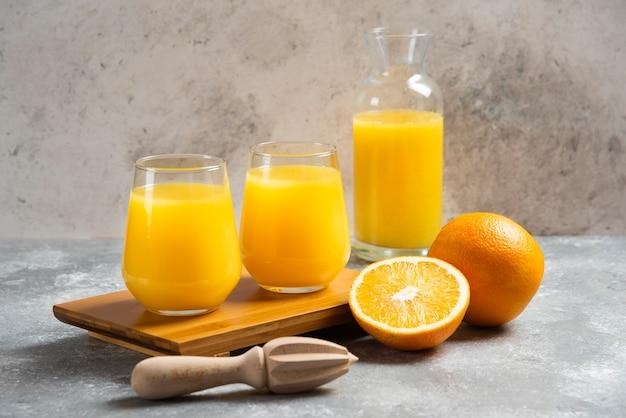 Um copo de suco de laranja e um alargador de madeira.