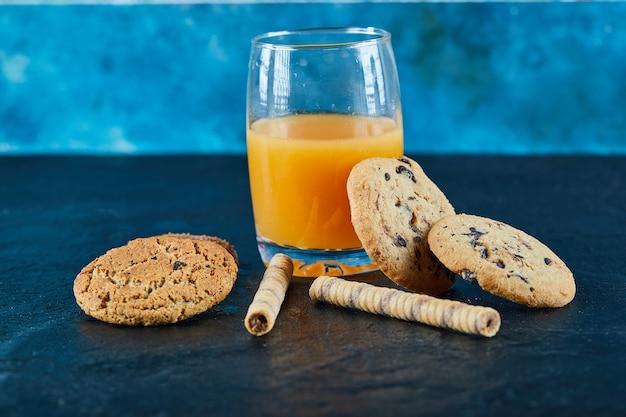 Um copo de suco de laranja e vários biscoitos na superfície escura
