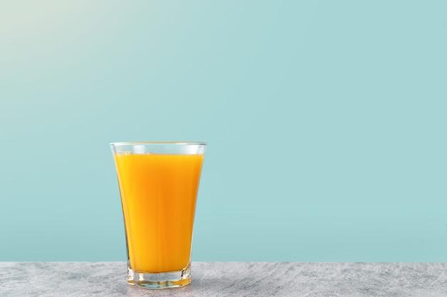 Um copo de suco de laranja em fundo amarelo claro