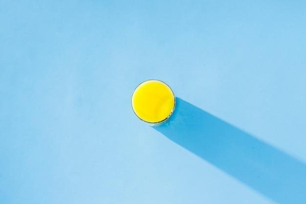 Um copo de suco de laranja em fundo azul. conceito de vitaminas, verão, tropical, bebida da sede. minimalismo. luz natural. vista plana leiga, superior.