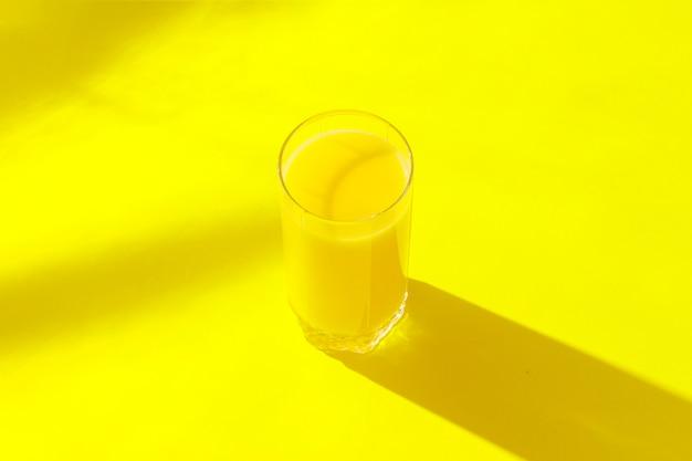 Um copo de suco de laranja em um fundo amarelo. conceito de vitaminas, verão, tropical, bebida da sede. minimalismo. luz natural. vista plana leiga, superior.