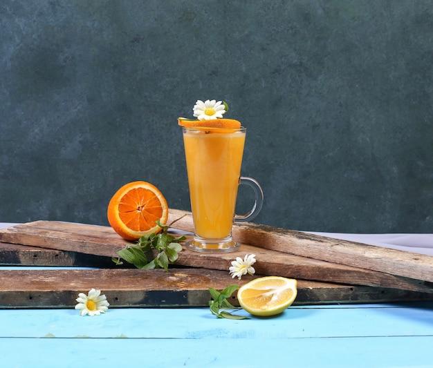 Um copo de suco de laranja em um pedaço de madeira.