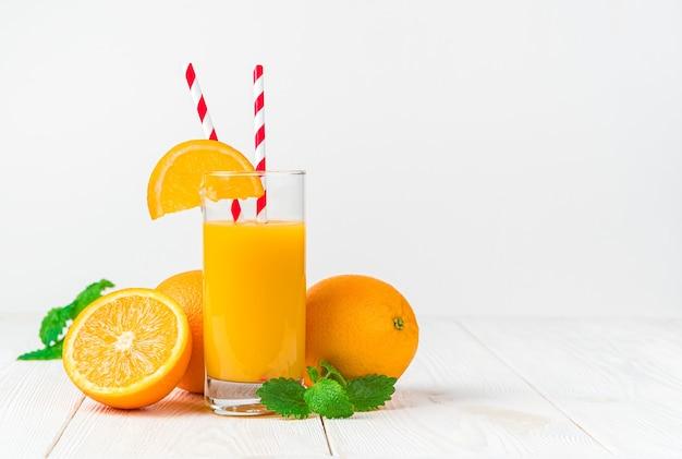 Um copo de suco de laranja espremido na hora com uma fatia de laranja e tubos em uma mesa leve com laranjas e hortelã.