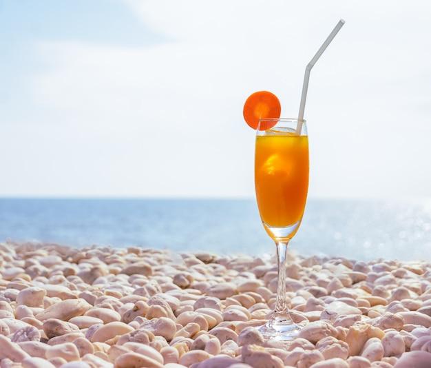 Um copo de suco de laranja fresco com gelo e fatia de cenoura na praia de seixos brancos