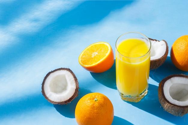 Um copo de suco de laranja, laranjas e cocos, sobre um fundo azul. conceito de vitaminas, verão, tropical, bebida da sede. luz natural. vista plana leiga, superior.
