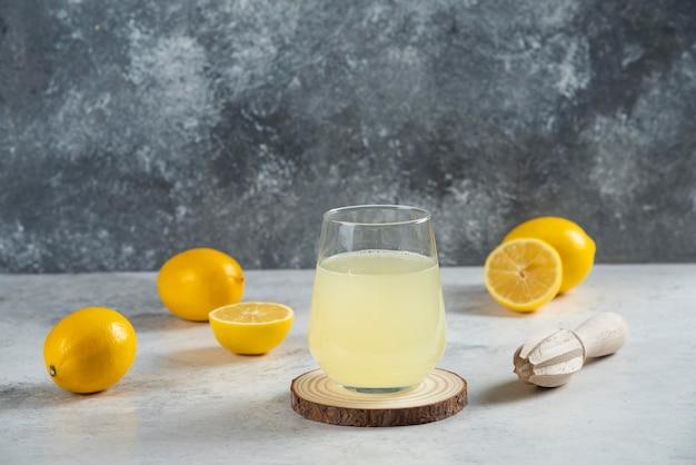 Um copo de suco de limão fresco em uma placa de madeira.