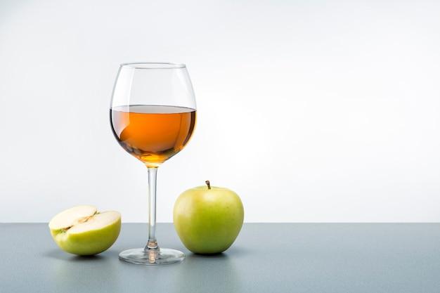 Um copo de suco de maçã com maçãs verdes em cima da mesa com espaço de cópia.
